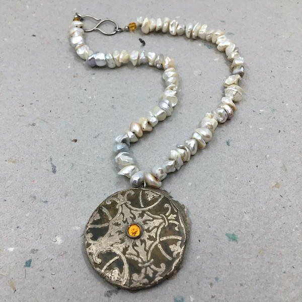 Necklace consisting of aged silver textured organic round pendant with small topaz stone set in the middle and organic freshwater pearl strand in shades of white, cream and grey with two small topaz stones on either size of a silver S clasp.