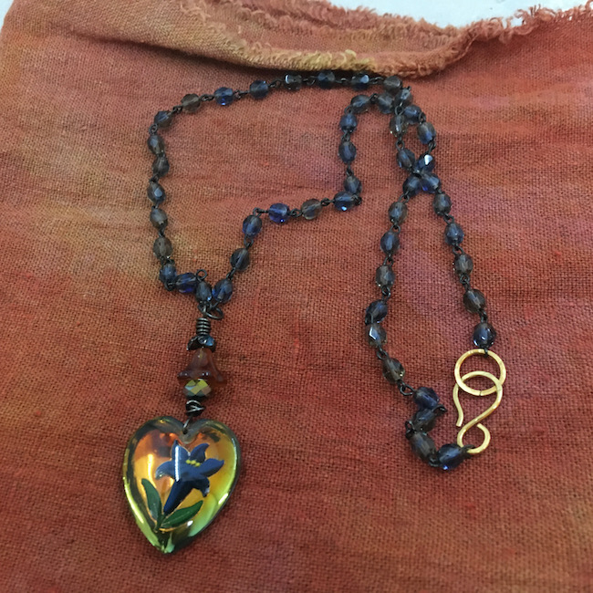 Rust colored fabric with a necklace on it. Heart pendant with a flower, blue glass beaded chain and a brass S clasp.