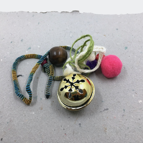 Kit materials including a gold tone jingle bell, various strings, wooden beads and pom-pom balls