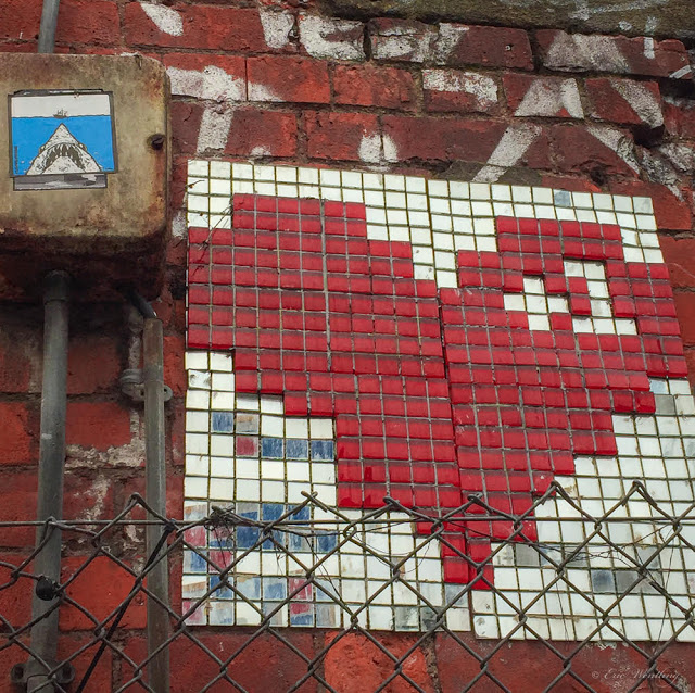 Photo by Eric Wentling of a brick wall with a a red tile heart behind a chain link fence. Also some pipes up to a box with the picture of a shark on it.