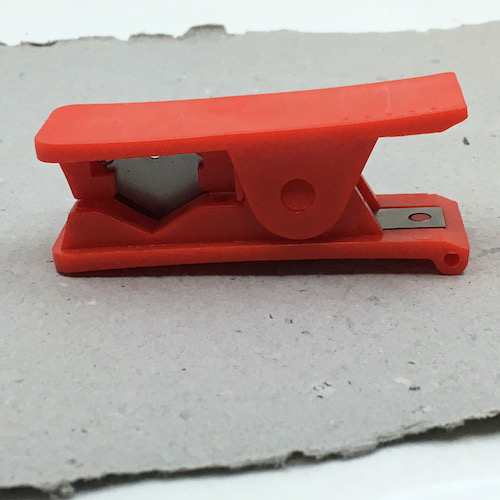 Red plastic and silver blade leather cutter tool