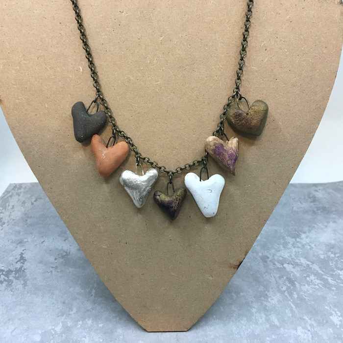 Necklace for with fine brass chain necklace showing 7 similar ceramic hearts in different colors.