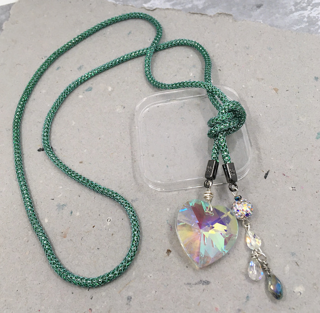Necklace made of teal SilverSilk jewelry wire into a lariat style with a large crystal heart on one side and various crystal and rhinestone beads on the other side.
