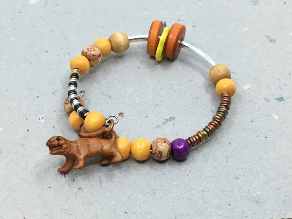 bangle bracelet with silver tone metal, coiled back, gold and silver wire, a variety of wooden beads, one yellow glass hoop, a bunch of metallic O rings and a wooden animal charm.
