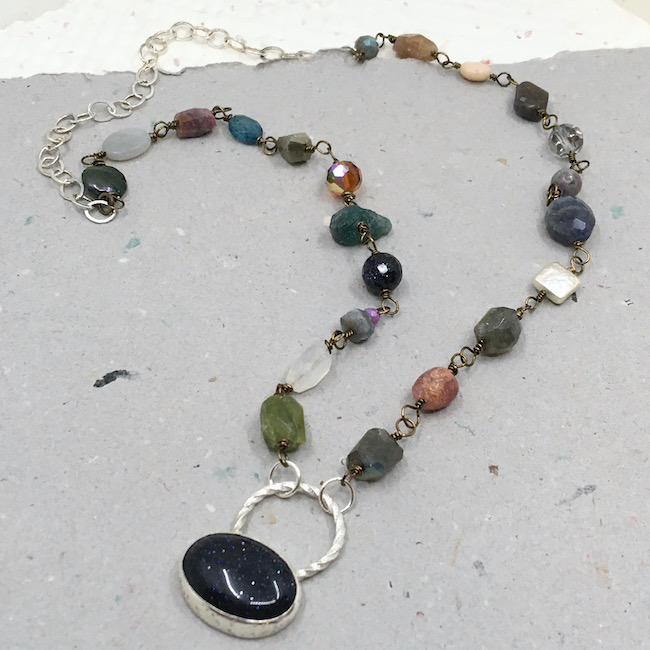 Necklace of mixed wire wrapped gemstones with silver chain at the back and a blue goldstone set cab in a silver setting with a large, twisted bail.