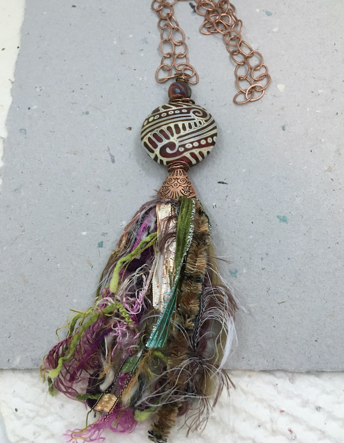 A wider shot of the necklace with copper chain and findings, a large, lentil shaped dark red and cream patterned focal and multiple colors and textures of fiber made into a tassel.
