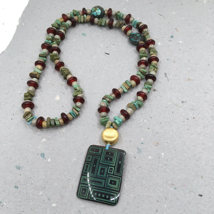 Etched shell pendant with necklace of glass seed beads, turquoise chip, horn discs and two larger oval turquoise beads.