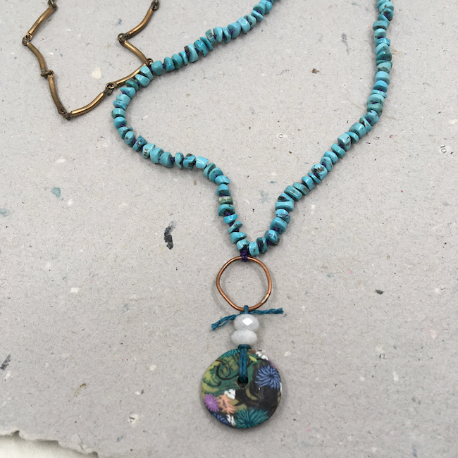 Necklace with colorful botanical disk pendant and two moonstone beads on a copper hoop. The rest of the necklace is turquoise and vintage brass chain.