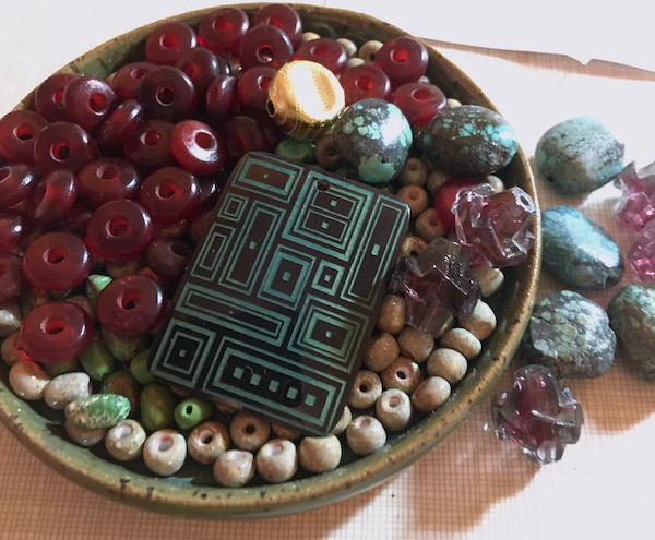 Dish with beads - turquoise, horn and glass. On top is a rectangular etched brown shell pendant with a modern design of different squares and rectangles in turquoise.