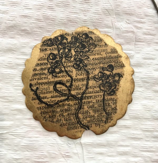Brass scalloped circle with old paper with text overstamped with a flora design in black.