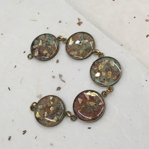 Circle bracelet links with green/rust paper and gold shards of glass glitter covered with resin.