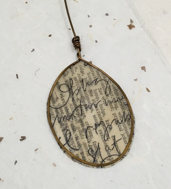 Oval wire bezel with old paper overstamped in black with cursive words.