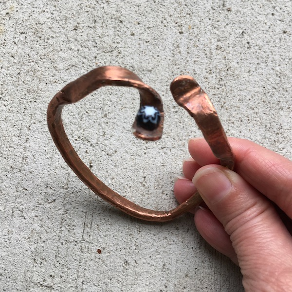 Copper bangle slightly open at top with one bead.