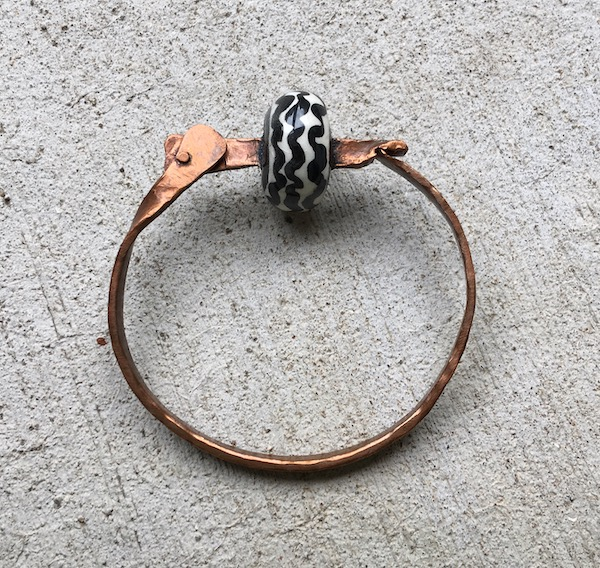 Copper hinged bracelet with black and white striped ceramic bead.