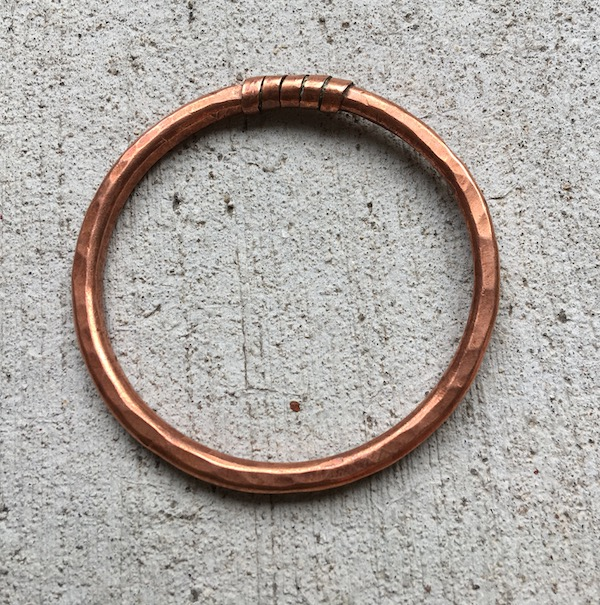 Pounded copper bangle with flat wire wound at top.