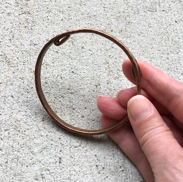 Copper bangle with folded ends.