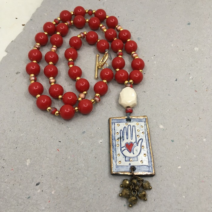 Rectangular ceramic heart in hand pendant that is white, blue and gold with sparkly small beads dangling from the bottom and small red/larger white bead above. Necklace part made of large red rounds and small gold spacers.