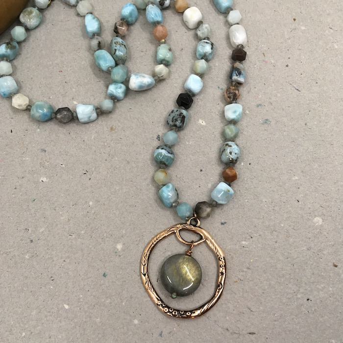 Bronze textured open frame pendant with coin labradorite bead inside. Necklace portion consists of a mix of larimar and amazonite for a mix of blue, brown, greenish, whitish, and cream colored beads.