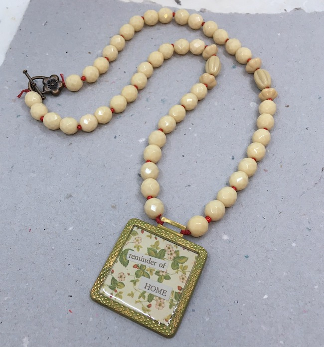 """Square metal pendant with strawberry print paper and words that say """"reminder of home"""" covered in clear resin. Necklace part is light beige beads with tiny red spacer beads."""