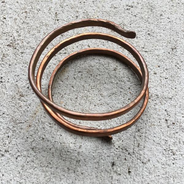 Triple wound copper bracelet shown on its side.