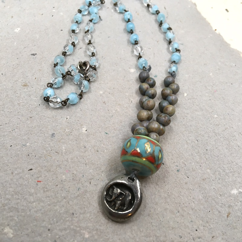 Necklace with silver elephant charm, blue, green, red and gold glass bead, earth tone glass beads and rosary chain with light blue glass beads.