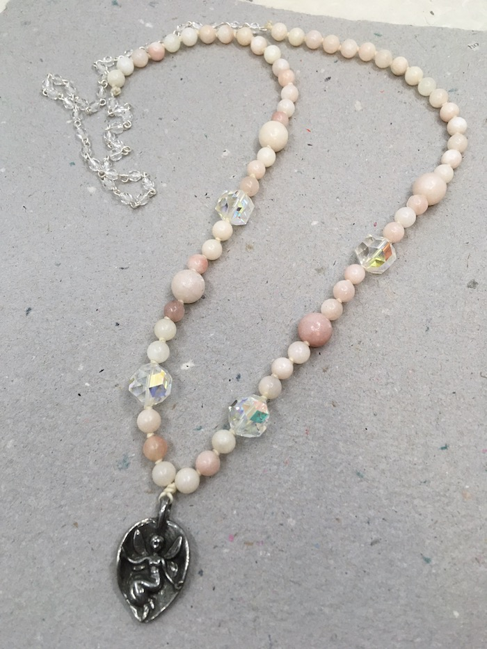 Necklace with silver fairy in a leaf pendant, very light pink round beads in two sized and large faceted crystal beads with small crystal rosary chain at back.