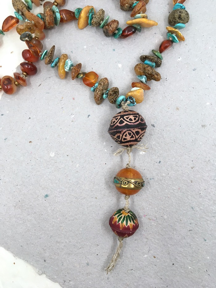 Necklace with three large beads knotted on a pendant. The rest of the necklace if amber chips alternated with turquoise chips and smooth agate.