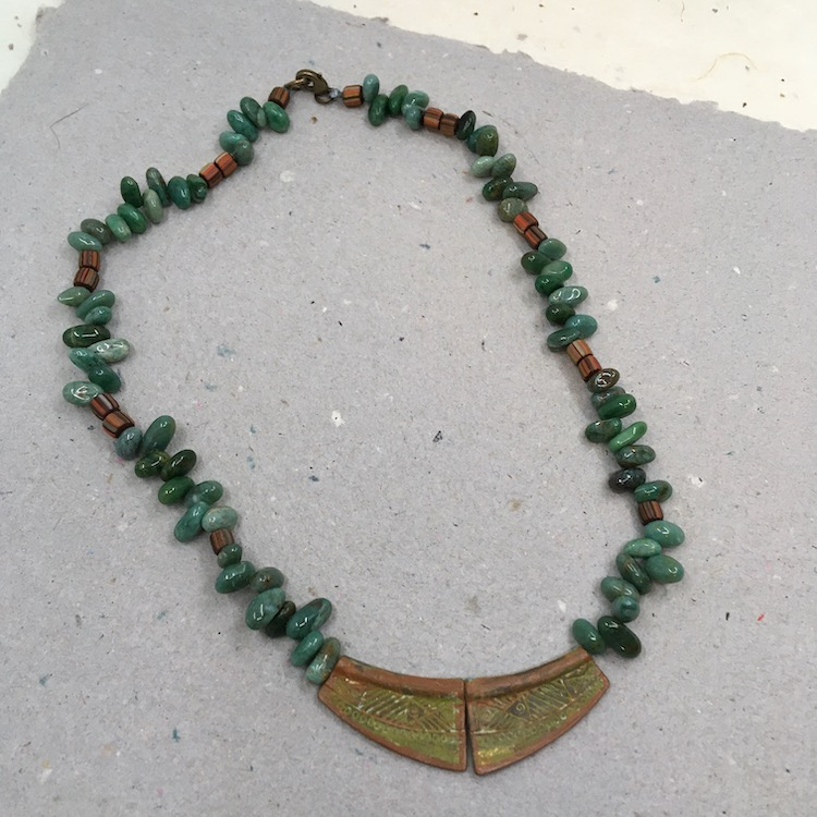 Necklace with two distressed, textured metal pieces in front, irregular green drops and small rust striped barrel spacers.