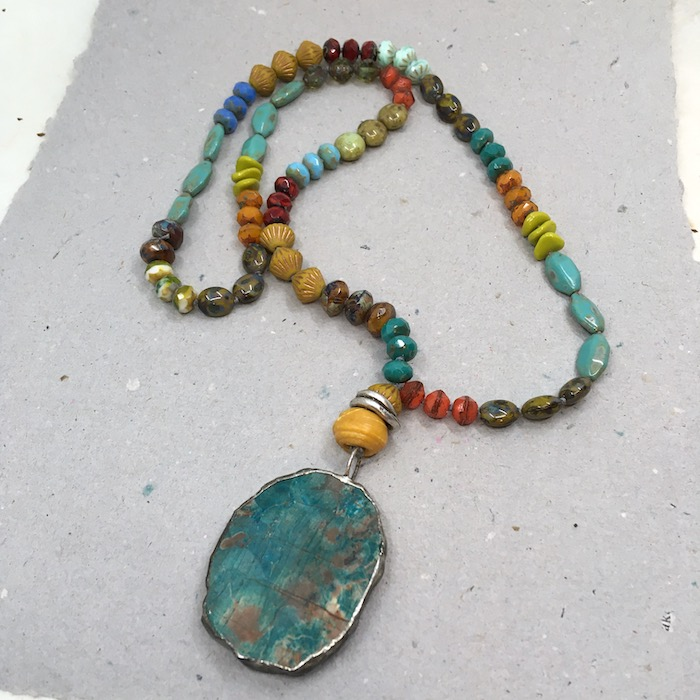 Mottled turquoise solder frame oval pendant with a variety of colors and shapes of Czech glass beads made into a necklace.