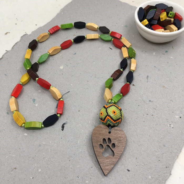 Wooden heart pendant with a paw print cut out with a yellow, orange and black beaded bead above it. The necklace is finished with seed beads and hexagon shaped wooden beads in yellow, brown, black, green and red.